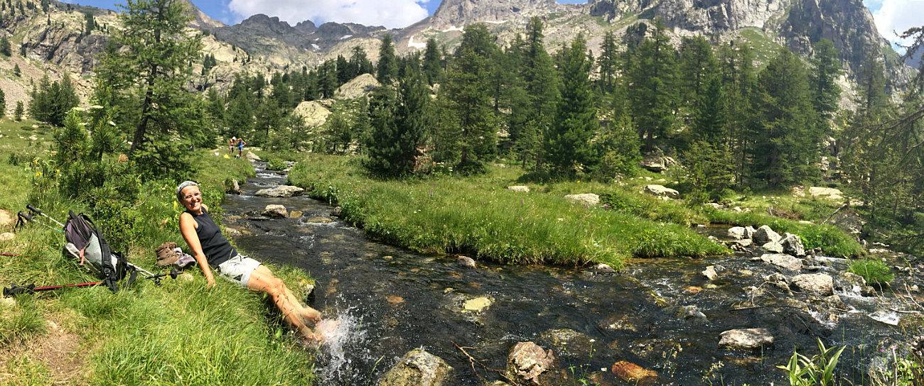 Amelie immerge i piedi nel fiume verso il lago Trecolpas