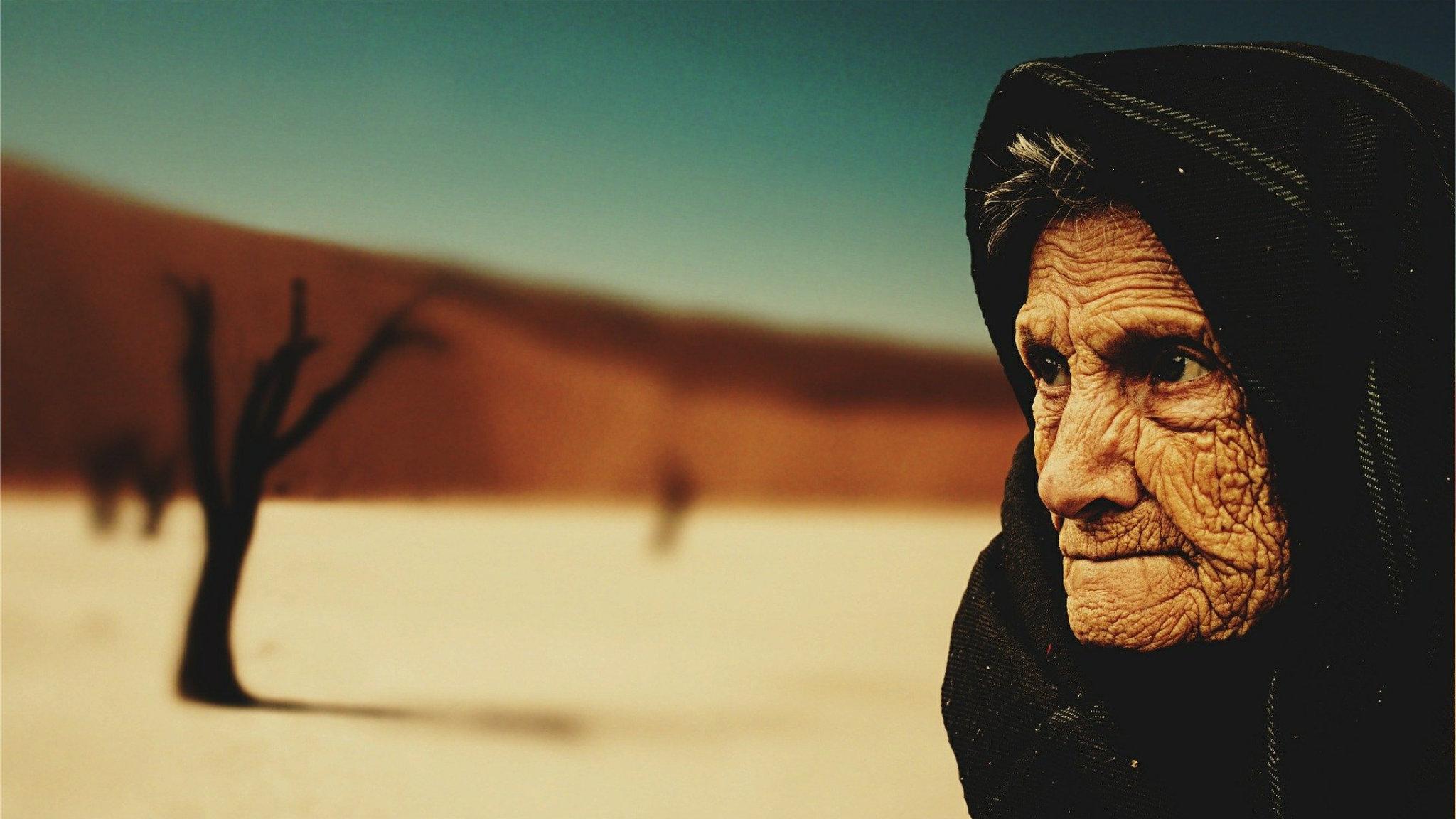 Un'anziana donna di fronte alle dune del Namib
